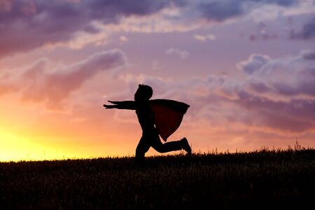 A young boy wearing a cape plays a super hero at sunset. photo