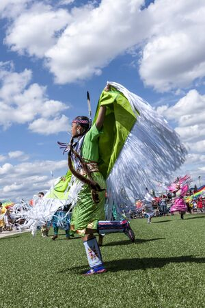 spreading arms: Coeur dAlene, Idaho USA - 07-23-2016. Young native woman spreading arms at dance. Young dancer participates in the Julyamsh Powwow on July 23, 2016 at the Kootenai County Fairgrounds in Coeur dAlene, Idaho. Editorial