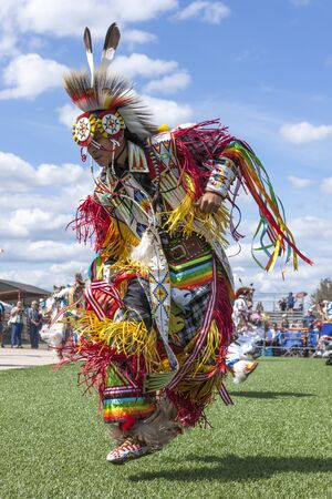 stepping: Coeur dAlene, Idaho USA - 07-23-2016. High stepping at the Julyamsh powwow. Young dancer participates in the Julyamsh Powwow on July 23, 2016 at the Kootenai County Fairgrounds in Coeur dAlene, Idaho. Editorial