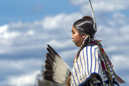 county side: Coeur dAlene, Idaho USA - 07-23-2016. Side view of Native American against blue sky. Young dancer participates in the Julyamsh Powwow on July 23, 2016 at the Kootenai County Fairgrounds in Coeur dAlene, Idaho.