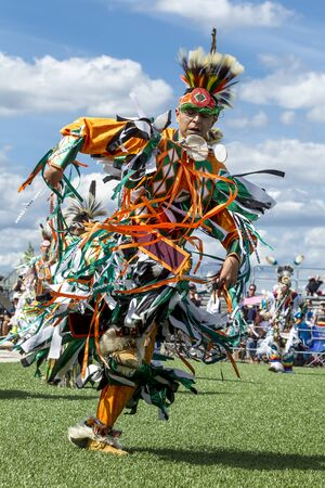 Coeur dAlene, Idaho USA - 07-23-2016. Colorfully dressed young man at powwow. Young dancer participates in the Julyamsh Powwow on July 23, 2016 at the Kootenai County Fairgrounds in Coeur dAlene, Idaho.