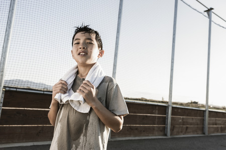 A confident boy with a towel around his neck after a hard practice looks ready for more.