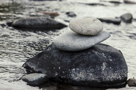 cairn: Small rocks stacked up into a rock cairn on a boulder the the river.