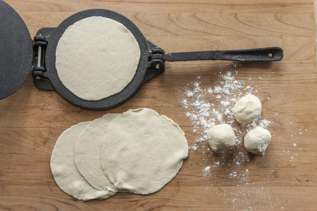 An overview of home made tortillas and a cast iron press. Stok Fotoğraf