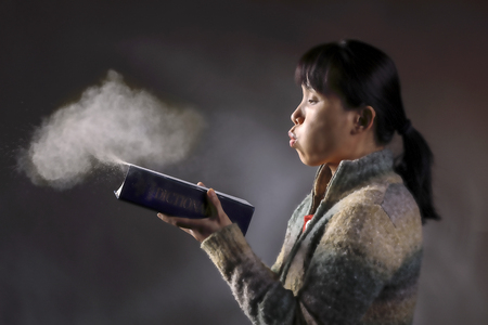 Asian woman blows dust off an old dictionary in this concept image. 版權商用圖片