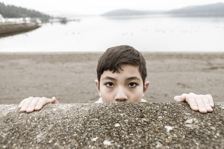 A conceptual image of a young boy peering over a wall by a lake.