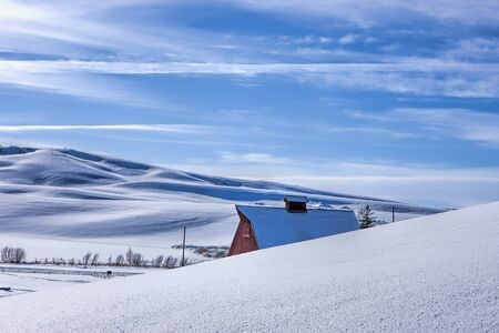 The roof of a red barn peaks over a snowy hill in this winter vista in Moscow, Idaho.