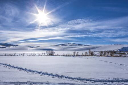 The sun shines in the blue sky over a snow covered farm field in Moscow, Idaho.
