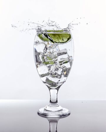 Lime splashes into glass of water.