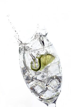 Slice of lime dropped into glass of water.