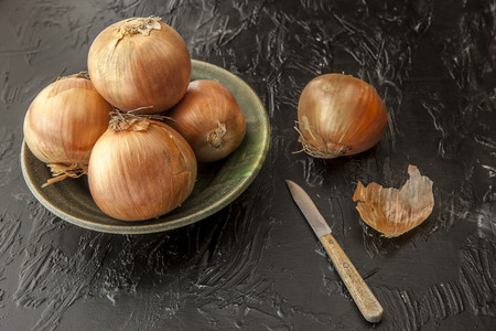 Whole yellow onions and a knife.