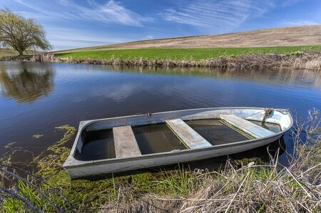 Old boat in pond in eastern Washington.
