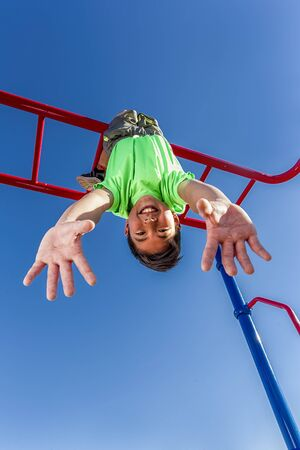 Boy hangs upside down while playing on the monkey bars. Stock Photo