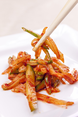 A close up image of sliced cucumbers mixed in red pepper paste and chopsticks.