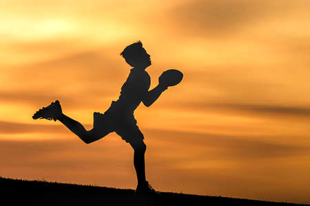 A young boy in silhouette is playing football at sunset against an orange sky.