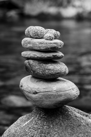 A black and white image of a well balanced rock cairn.