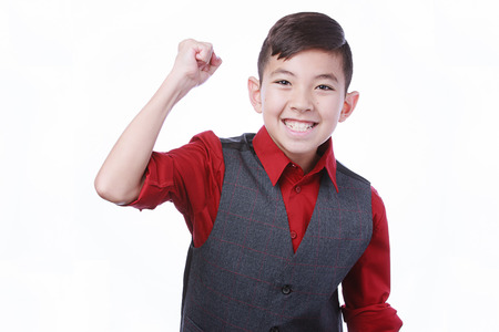 A happy young boy makes a fist pumping gesture.