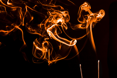 Conceptual image of orange incense smoke floating around.