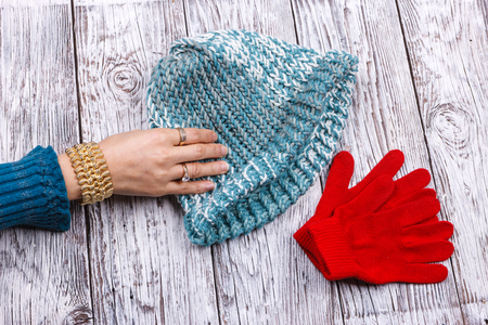 A womans hand is reaching for the wool knit hat y the red gloves. Reklamní fotografie