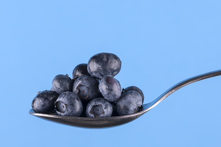 Nice plump blueberries piled up on a spoon set against a blue background.