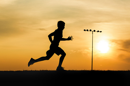 An athletic boy runs on a field at sunset in north Idaho.