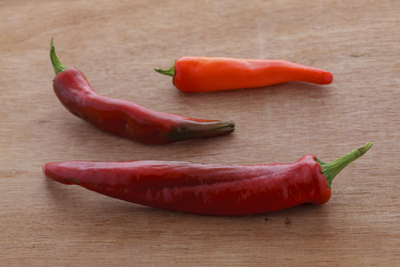 A close up of three red spicy peppers on a wood background.