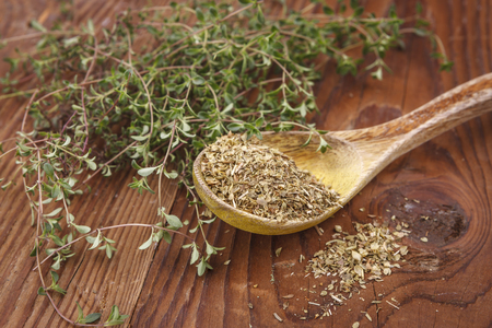 Display of dried thyme leaves on a spoon surrounded by fresh thyme leaves.