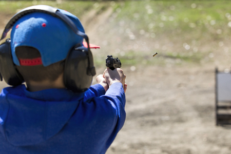 A boy safely practices shooting a pistol at a range in north Idaho.