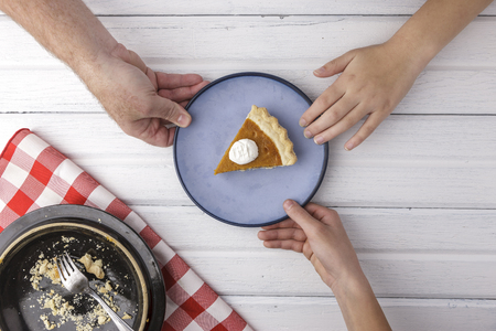 An overview of hands reaching for the last piece of pumpkin pie. Stock Photo