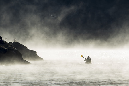 A kayaker paddles though the mist and fog in early December on Coeur d'Alene Lake by Higgens Point in North Idaho. 版權商用圖片