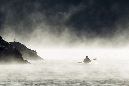 A kayaker paddles though the mist and fog in early December on Coeur d'Alene Lake by Higgens Point in North Idaho. Stok Fotoğraf