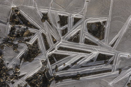 An overhead closeup of abstract ice formations on the ground.