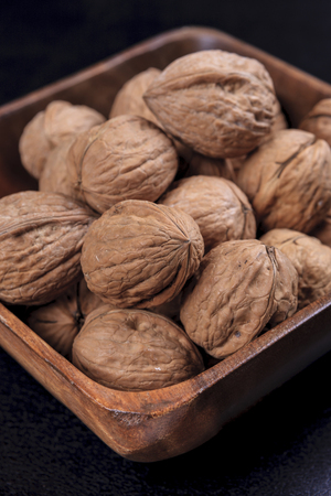 A close up photo of unshelled walnuts in a wooden bowl.