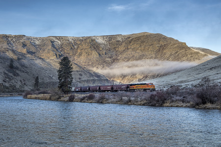 A freight train moves through a canyon by the Yakima river in central Washington.