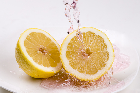 A concept photo of pouring red tinted water  onto lemon halves.