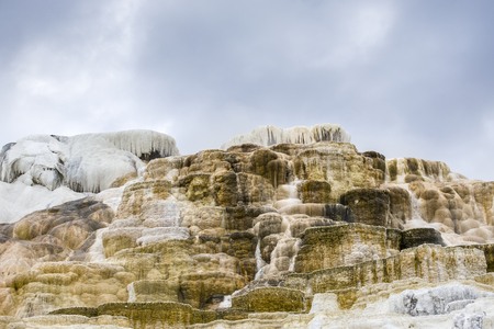 The calcium and mineral deposits under a cloiudy sky at Mammoth hot springs in Yellowstone National Park. Фото со стока