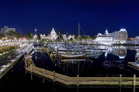 A boardwalk leads around the boats at the inner harbor on a calm evening in Victoria BC, Canada.