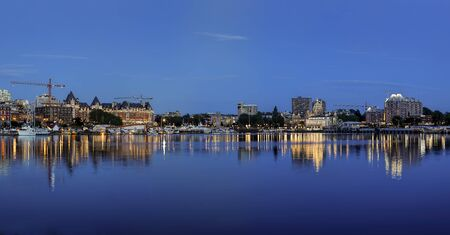 A panorama photo of the inner harbor at dusk in Victoria, BC Canada.