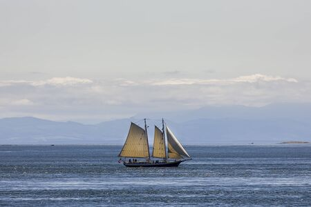 A vintage style two masted sailing ship out on the open waters in the San Juan Islands.