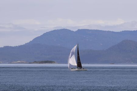 A sailboat takes advantage of a beautiful day in the waters of the San Juan islands in Washington state.