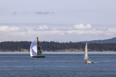 Sailboats taking advantage of a beautiful day in the waters of the San Juan islands in Washington state.