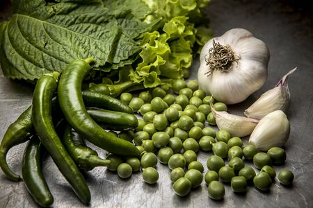 A close up studio image of an assortment of vegetables such as garlic, lettuce, peas, and peppers. Stockfoto