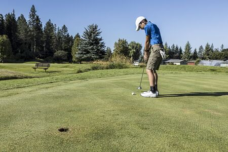 An older boy swings back for a putt on a bright and sunny day in Coeur d'Alene, Idaho. Standard-Bild