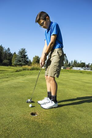 An older boy makes a short putt on a bright and sunny day in Coeur d'Alene, Idaho. 免版税图像