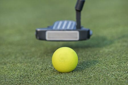 A close up photo of a putter getting ready to strike the golf ball.
