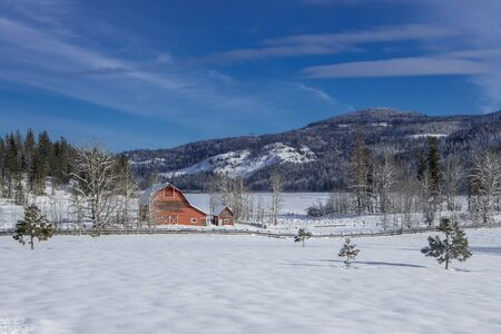 A small red barn stands in a snow covered field in north Idaho.