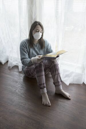 A concept photo of a teen girl with a mask, gloves,  and a book showing the boredom of staying at home during the quarantine orders.