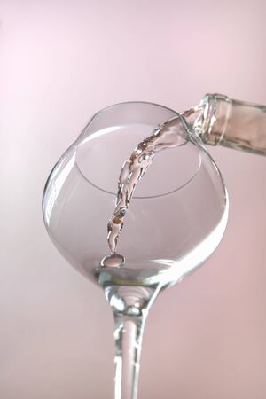 A concept studio image of pouring rose wine into a wine glass. Stockfoto