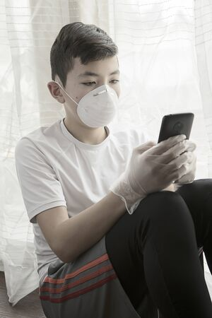 A concept photo of a teen boy with a mask, gloves,  and a cell phone showing the boredom of staying at home during the quarantine orders Stockfoto