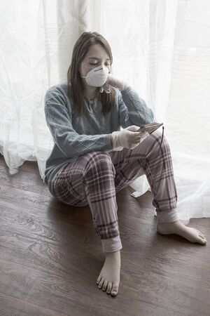 A concept photo of a teen girl with a mask, gloves,  and a cell phone showing the boredom of staying at home during the quarantine orders. Stockfoto